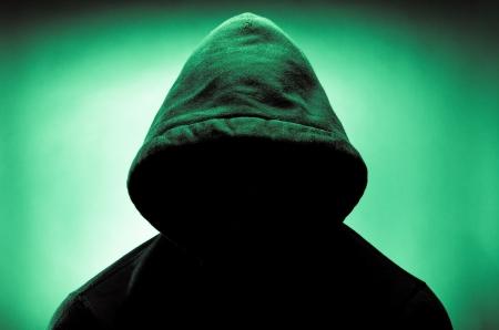 影で顔を持つフードをかぶっている男 写真素材