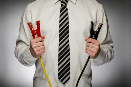 Man wearing tie holding jumper cables photo