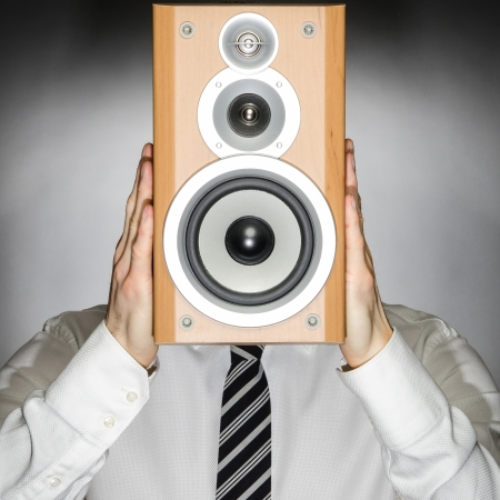 Man wearing a tie holding a speaker in front of his face Stock Photo