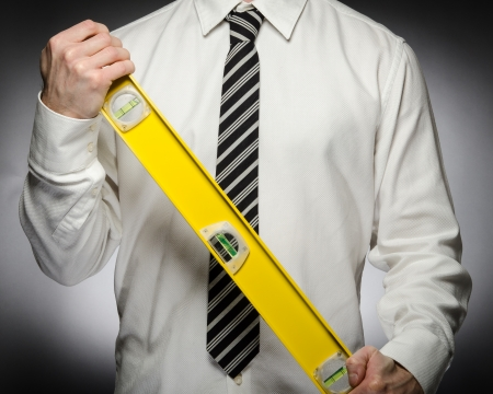 Man wearing tie holding a large level