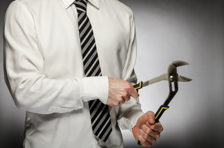 Man wearing a tie holding a wrench photo