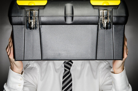 Man wearing a tie holding a toolbox photo