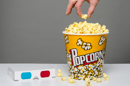 couch potato: Hand reaching for popcorn with 3d glasses