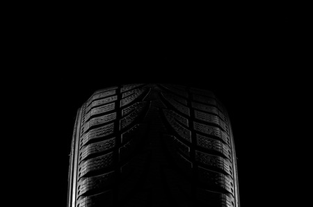 all weather: Tire lit on black Stock Photo