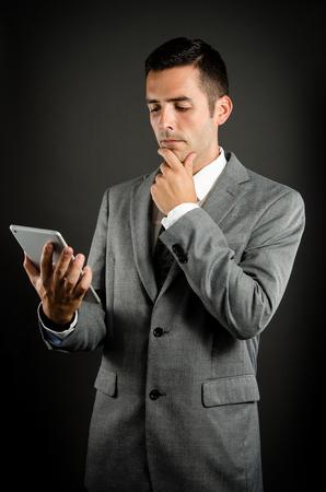 hardworking: Thinking holding tablet