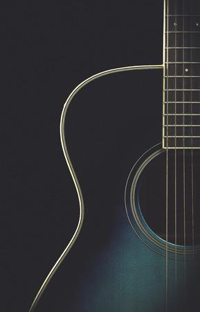Half of a guitar on black matte finish Stock Photo