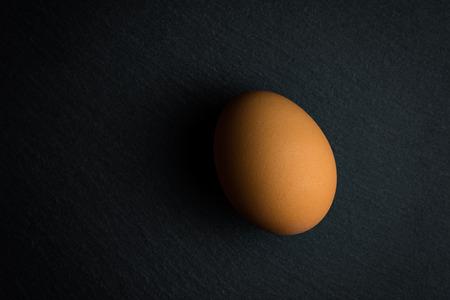 Single egg on black Standard-Bild