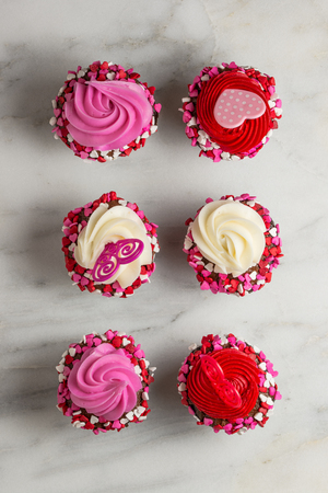 Many cupcakes with hearts on white marble