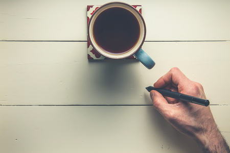 Top view of hand with pen and coffee on wood Stock Photo
