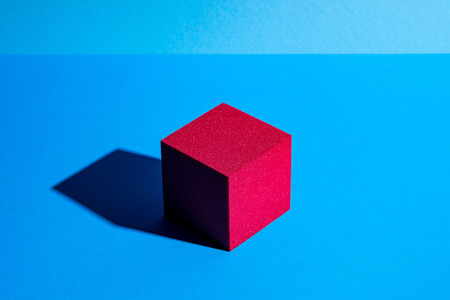 Red cube with shadow on blue Standard-Bild