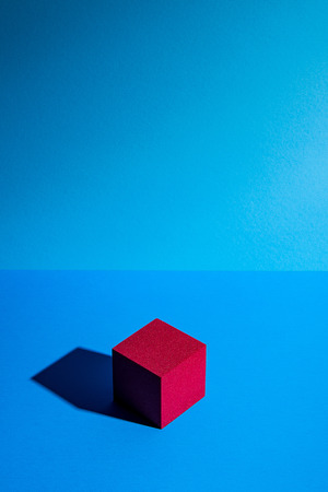 Abstrakter roter Würfel auf blauem Hintergrund Standard-Bild - 87155367