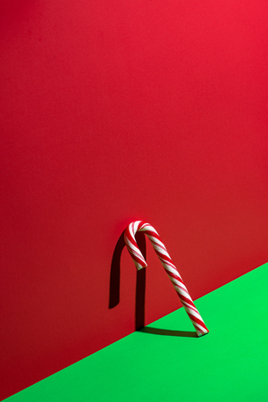 Leaning candy cane on red and green Standard-Bild