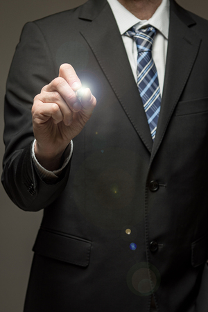 Man wearing suit touching virtual screen with pen tool Standard-Bild - 102907464