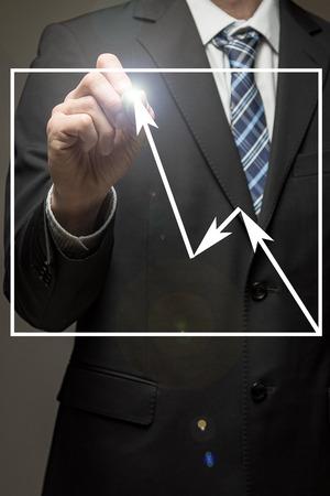 Man wearing suit drawing graph showing an increase Standard-Bild