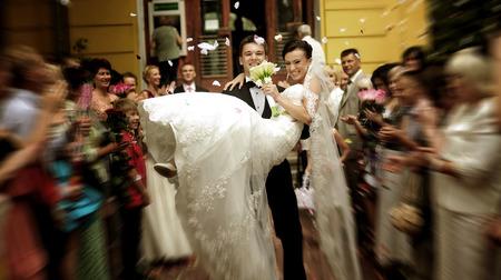registrar: Happy groom brings the bride in his arms from the registrar