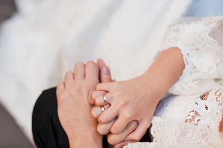 Mains mariés avec des alliances sur la texture de fond en bois Banque d'images - 94596043