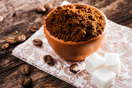 Fresh-ground coffee beans.Coffee beans on wooden texture.A cup of ground coffee Stock Photo