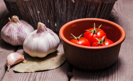 Fresh garlic and red tomatoes Closeup shot on wooden table Banco de Imagens