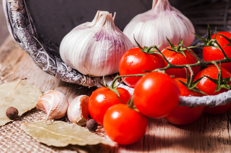 Closeup shot fresh garlic and tomatoes on wooden table Banco de Imagens