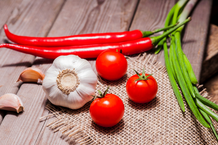 Fresh garlic, red tomatoes, pepper closeup shot on wooden table Banco de Imagens