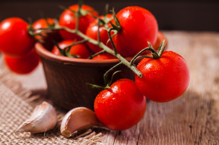 Fresh Tomatoes and garlic closeup shot on wooden table Banco de Imagens