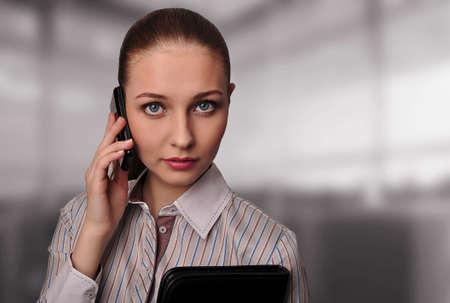 Business woman with a mobile phone and documents in the office photo