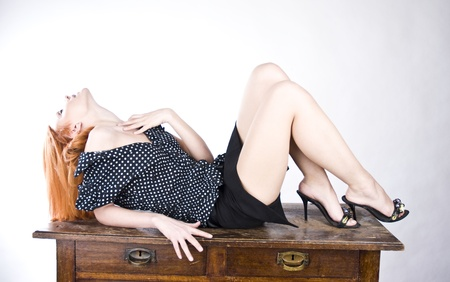 beautiful businesswoman on a table in sexy posed photo