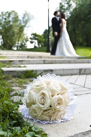 Wedding bouquet with the wedding couple in the background photo