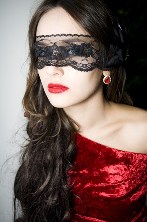 Lady in red dress with lace on a face  photo