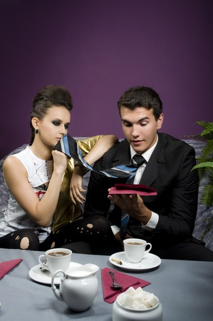 The girl uses a tie of the guy instead of a napkin  photo