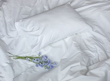 Flores en la cama desordenada, ropa de cama blanca y bouqet de flores azules, composición fotográfica creativa con cama blanca y ramillete, ramo de flores azules en la cama, bouqet romántico en la cama