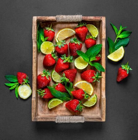 Strawberry fruit, mint leaves, lime and lemon halves on a vintage wooden tray. Mojito or lemonade mix on the rustic wooden salver