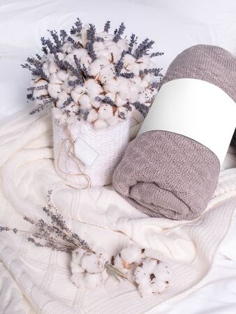Creative composition with rolled blankets, cotton and lavender flowers. Brown and white plaids on the bed. Cozy set of bedding and flowers.