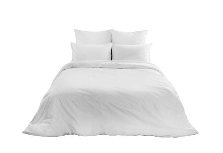 White bedlinen on a white bed isolated. Bedroom with bed and linen. Bed with pillows and duvet isolated. Banco de Imagens