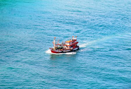 Fisherman ship in a open sea with blue clear water. Asia region. Top view. Stock Photo