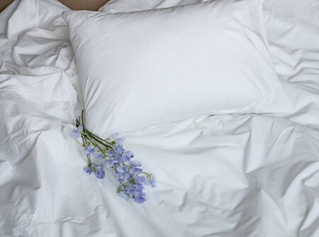 Fleurs sur le lit en désordre, articles de literie blancs et bouquet de fleurs bleues, composition photo créative avec lit blanc et bouquet de fleurs bleues sur la literie, bouquet romantique sur le lit
