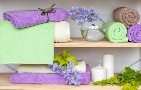 Set of different colors terry towels with blue flowers and candles on wooden shelfs. Rolled green, purple, beige and stack of different colors terry towels. Creative bath and SPA composition.