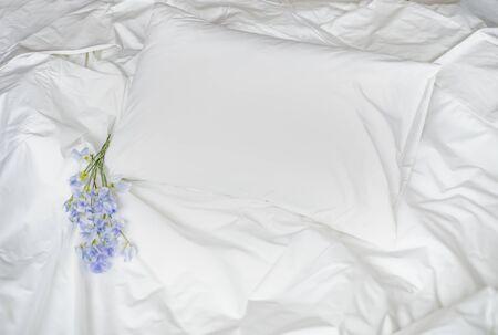 Flores en la cama desordenada, ropa de cama blanca y bouqet de flores azules, composición fotográfica creativa con cama blanca y ramillete, ramo de flores azules en la cama, bouqet romántico en la cama Foto de archivo