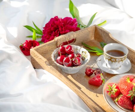 Peony and wooden rustic tray with bowls of strawberries and sweet cherry and cup of coffe on a white bedlinen. Morning mix of fruits, flowers an cup of cofee on a bed