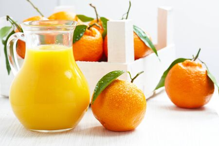 Orange juice in pitcher and tangerines photo
