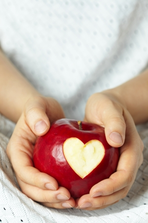 Hand with apple, which cut heart photo