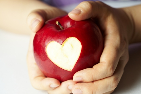 heart shape with hands: Hand with apple, which cut heart
