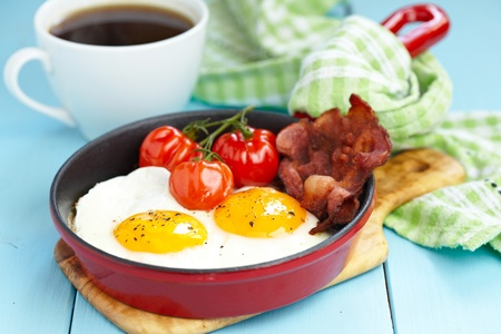 bacon and eggs: Fried eggs with bacon and tomatoes Stock Photo