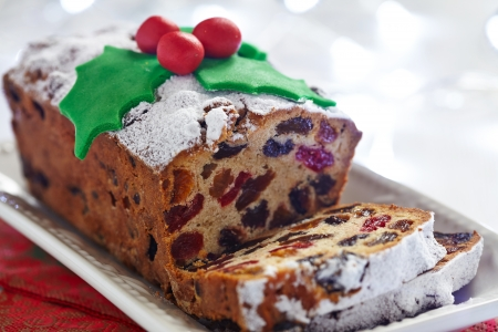 christmas food: Christmas fruit cake decorated with holly and berries