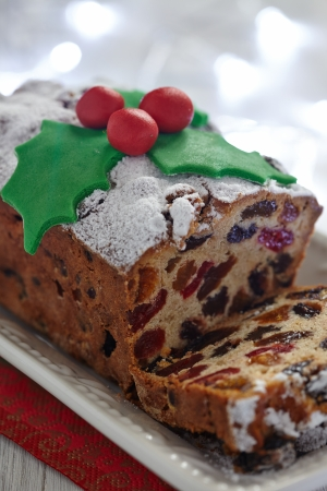fruitcake: Christmas fruit cake decorated with holly and berries