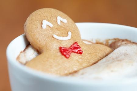 fondo chocolate: Hombre galleta de jengibre en una taza de cappuccino