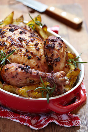 whole chicken: Whole roasted chicken with potatoes in red baked dish Stock Photo