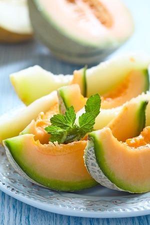 マスクメロン: Cantaloupe melon slices on blue wooden table