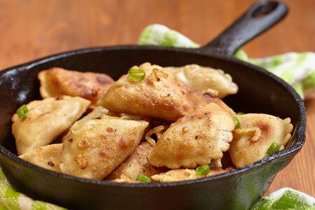 pierogi: Homemade dumplings fried with onion on a pan Stock Photo