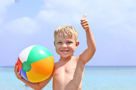 blond boy: Happy boy holding ball on the beach